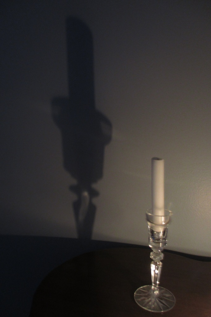 Artsy shot of a candle casting a neat shadow on the wall.